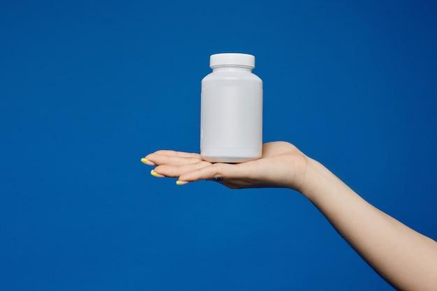 Mano femminile ordinata con il manicure con un barattolo di vitamine sul palmo, isolato su un blu con spazio di copia. il farmaco contro il virus sul palmo di una mano femminile. confezione con medicina antinfluenzale