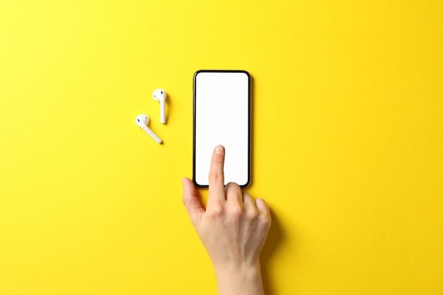Mano femminile, telefono con schermo vuoto e auricolari sulla superficie gialla