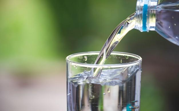 Mano femminile versando acqua dalla bottiglia al vetro su sfocatura sfondo