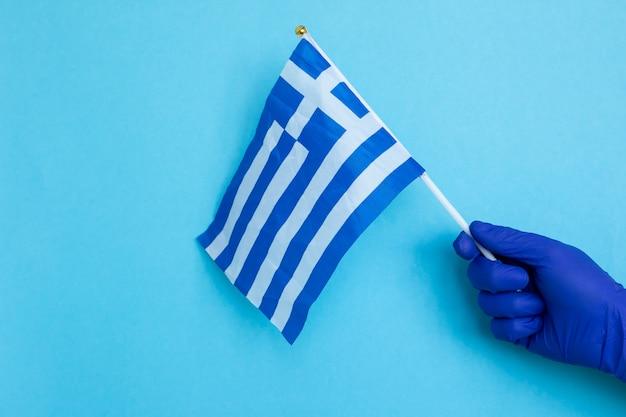Mano in guanti di lattice blu con bandiera greca isolato su blu, coronavirus, malattia, infezione, quarantena,