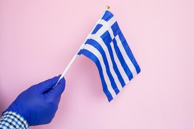 Mano in guanti di lattice blu con bandiera greca isolato su rosa, coronavirus, malattia, infezione, quarantena,