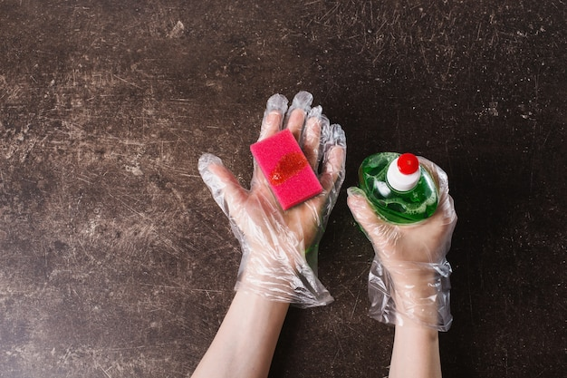 Mano in guanti di plastica igienica con una spugna su uno sfondo di marmo scuro. metti in ordine la casa. lavare i piatti con detergente