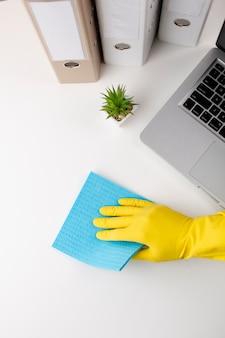 Mano in guanti per la pulizia della scrivania