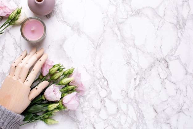 Mano in legno con fiori rosa su marmo