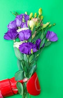 Mano in un guantone da boxe rosso in possesso di un mazzo di fiori