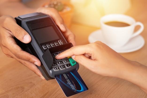 Mano inserendo il codice pin della carta di credito per la password di sicurezza nella macchina di scorrimento della carta di credito