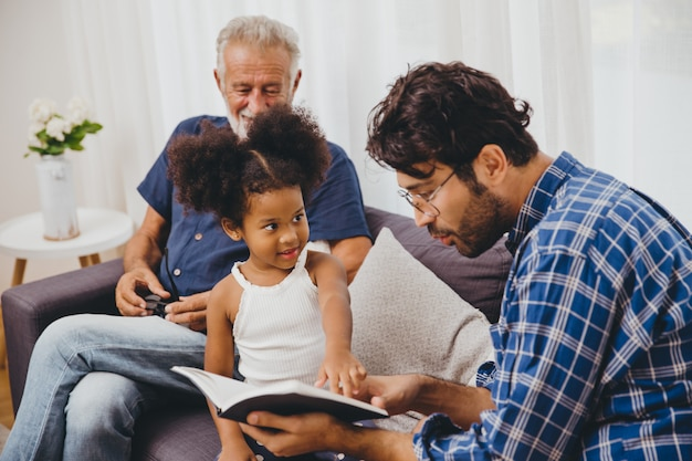 Mano intelligente della bambina del bambino geniale che indica al contenuto al libro per insegnare al suo genitore.