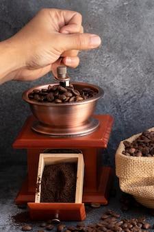 Mano macinando chicchi di caffè in smerigliatrice di legno