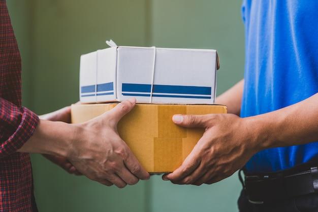 Mano maschile che accetta una consegna di scatole da fattorino.