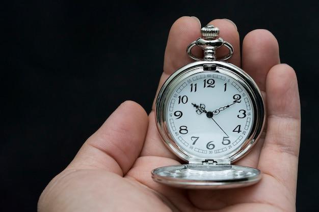 Mano maschile che tiene antico orologio da tasca. isolato su sfondo nero
