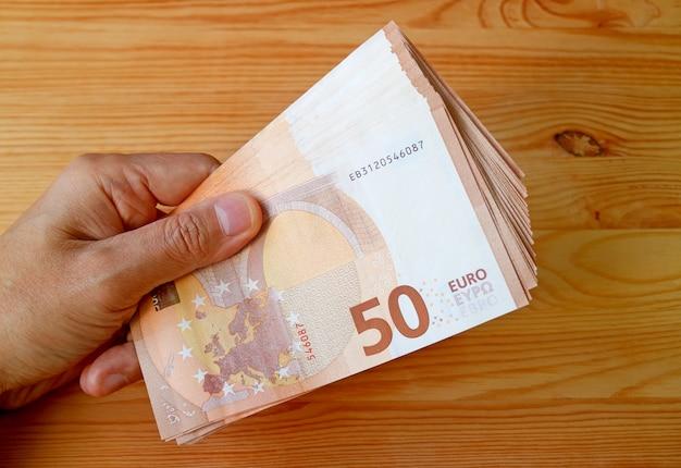Mano maschile che tiene un pacchetto di 50 banconote in euro su legno