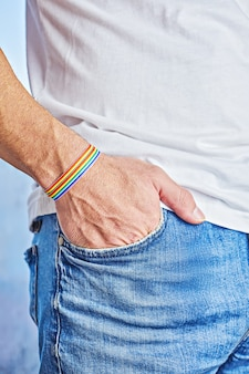 Mano maschile con bracciale arcobaleno e orgoglio testo nella tasca dei jeans