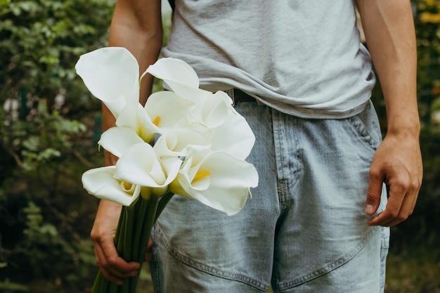 Mano maschile con fiori di gigli di calla