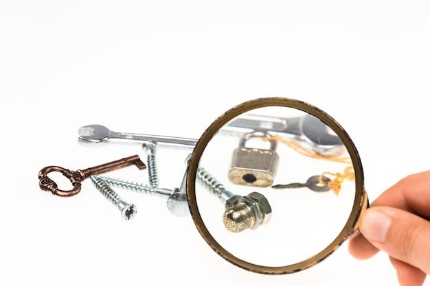 Mano maschile con lente d'ingrandimento e oggetti