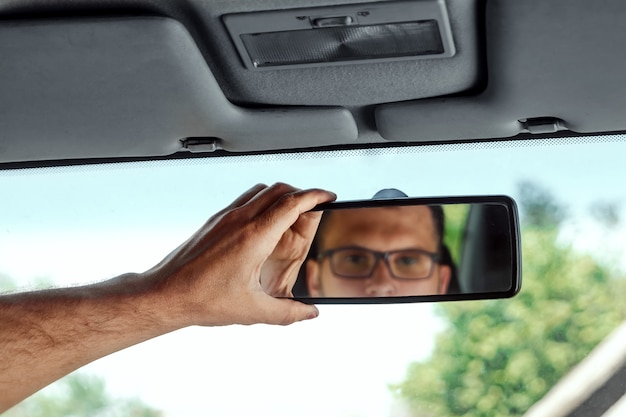 Mano maschile sullo specchietto retrovisore di un'auto