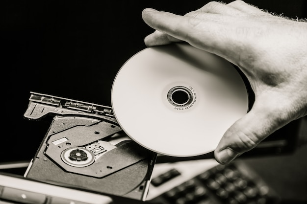 Mano maschio che inserisce un dvd in un'unità disco. bianco e nero