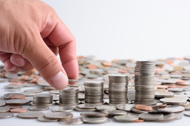 Mano maschio che mette le monete con i soldi crescenti di risparmio di crescita di punto della pila dei soldi, affare di finanza di concetto