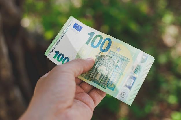 Mano maschio che tiene la centesima banconota in euro sulla parete verde