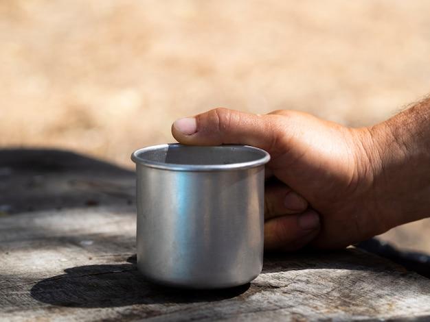 Mano maschio che tiene la tazza d'annata del metallo il giorno soleggiato