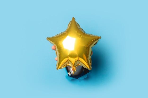 Mano maschio che tiene un palloncino dorato su sfondo blu