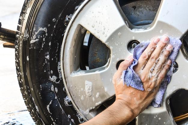 Mano maschio con l'automobile della ruota di lavaggio del panno blu
