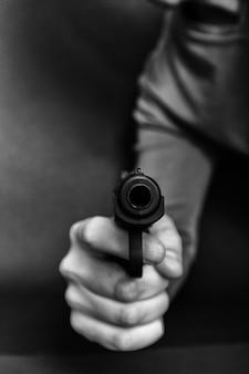 Mano maschio con la pistola isolata su fondo nero. l'uomo con una pistola pronta a sparare, si concentra sull'arma.