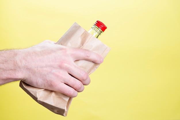 Mano maschio con una bottiglia di alcool in un sacco di carta su giallo