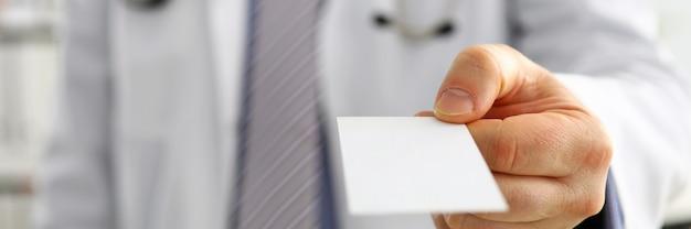 Mano maschio del medico che tiene e che dà la carta di chiamata in bianco bianca