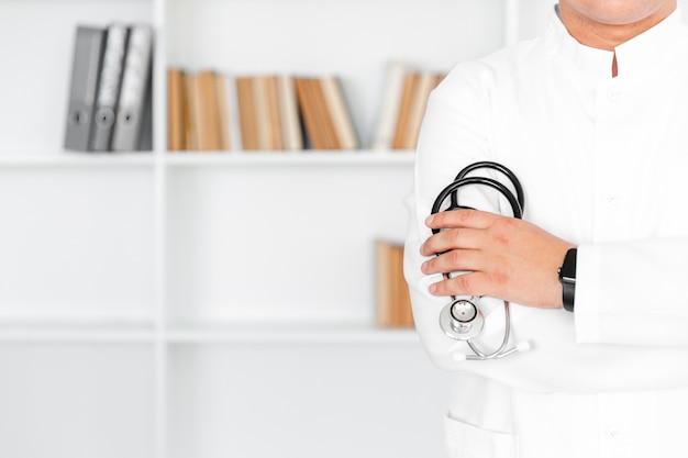Mano maschio del medico che tiene uno stetoscopio