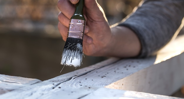 Mano maschio dipinge con vernice bianca su legno, concetto di pittura, primo piano, posto per il testo