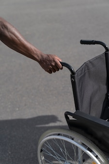Mano maschio nera che tiene sedia a rotelle isolata sulla strada