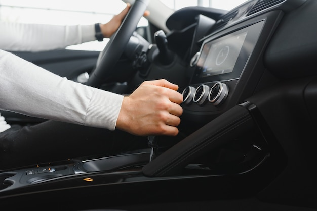 Mano maschio sulla leva del cambio della trasmissione in macchina