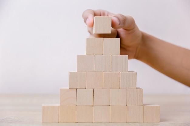 Mano mettendo blocco cubo di legno sulla piramide superiore.
