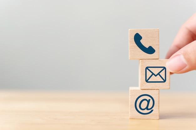 Mano mettendo il cubo di blocco di legno simbolo telefono, e-mail, indirizzo.