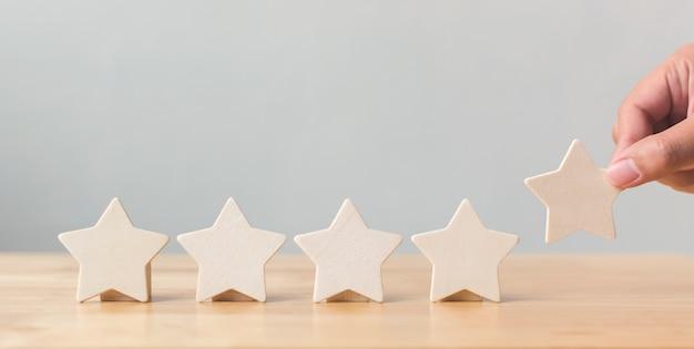 Mano mettendo in legno a cinque stelle sul tavolo