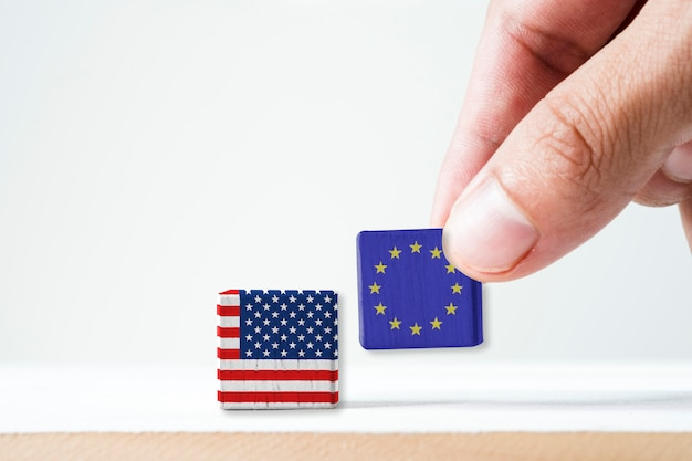 Mano mettendo la schermata di stampa bandiera europea e cubicolo di legno bandiera usa.e 'simbolo di stati uniti d'america aumentare la barriera fiscale tariffaria per il prodotto di importazione dai paesi dell'ue