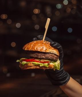 Mano nei guanti dell'hamburger che tengono l'hamburger di manzo nel fondo nero
