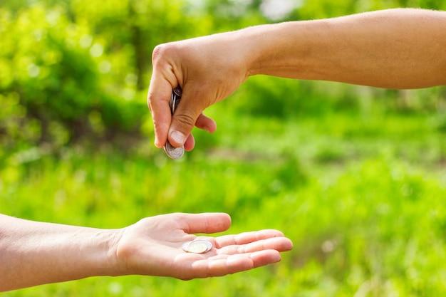 Mano nella mano dà monete su sfondo verde, concetto di finanza e prestiti.