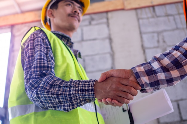 Mano nella mano tra gli appaltatori del progetto e i clienti a causa della negoziazione di spese e investimenti, costruzione e riparazione di edifici residenziali.