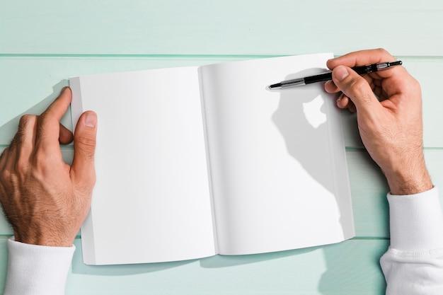 Mano piana di disposizione che tiene una penna sopra la lavagna per appunti dello spazio della copia