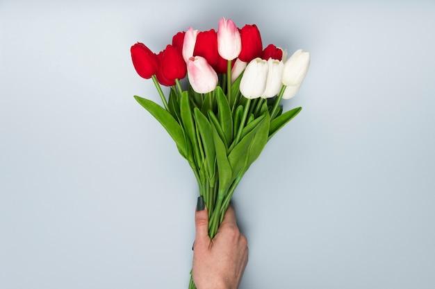 Mano piatta laica con bouquet di tulipani