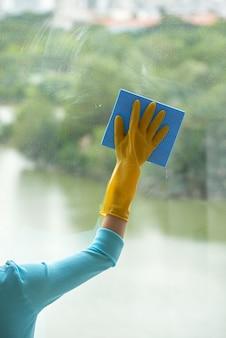 Mano potata della donna irriconoscibile che pulisce finestra panoramica