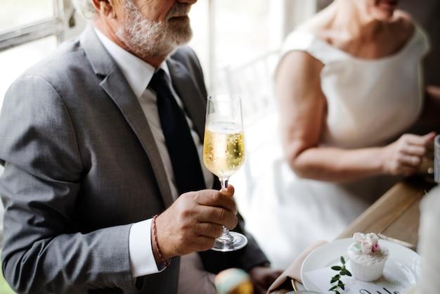 Mano senior della sposa che tiene il vetro di vino di champagne