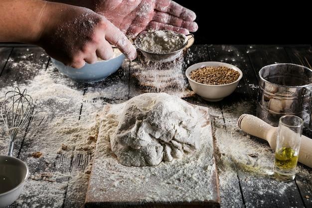 Mano setaccia la farina sulla pasta sul tavolo
