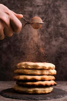 Mano setacciare il cacao in polvere sopra i pancake impilati