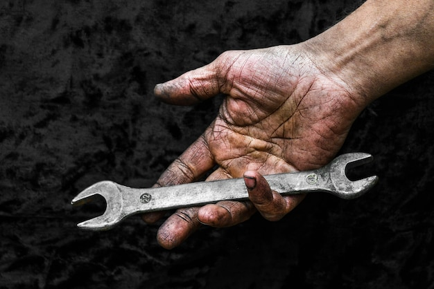 Mano sporca del lavoratore con la chiave inglese nell'officina di riparazione dell'automobile