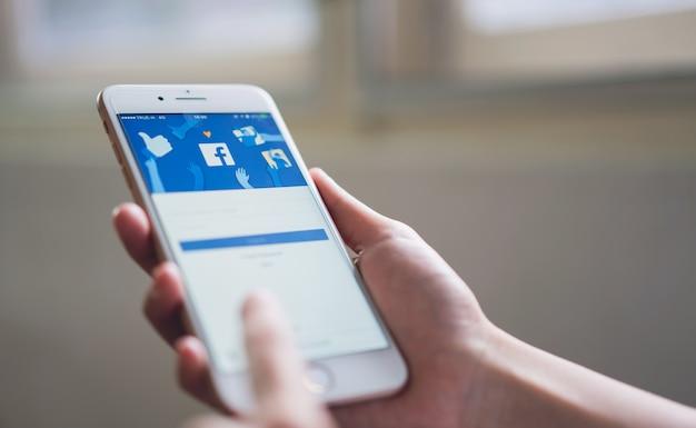 Mano sta premendo lo schermo di facebook su apple iphone 6,
