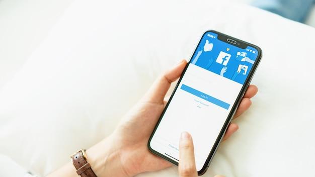 Mano sta premendo lo schermo di facebook su apple iphone x, i social media stanno usando per informa