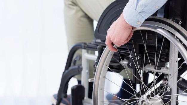 Mano sul primo piano della ruota di sedia a rotelle