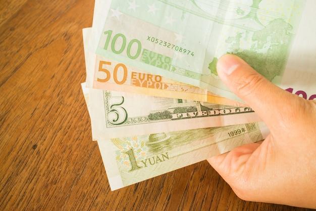 Mano sulla banconota di valute di nternational sulla tavola di legno